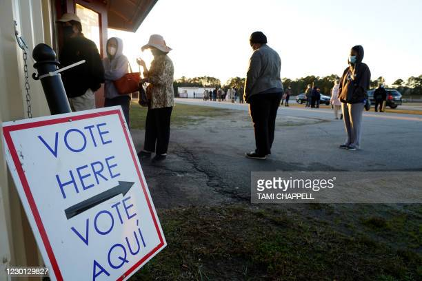 Voters stand in line to cast their ballots during the first day of early voting in the US Senate runoff at the Gwinnett Fairgrounds, December 14 in...
