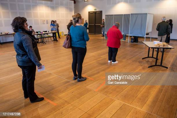 Voters stand on markers to keep them at least one metre apart prepare to cast their ballot in a polling station, set up ahead of the French mayoral...