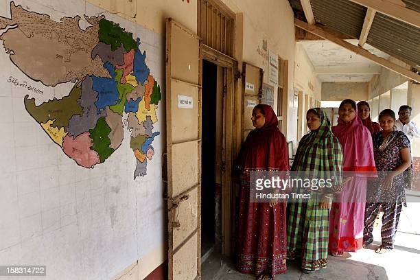 Voters standing in queue for casting their vote during the first phase polling of Gujarat assembly election at Viramgam on December 13 2012 in...