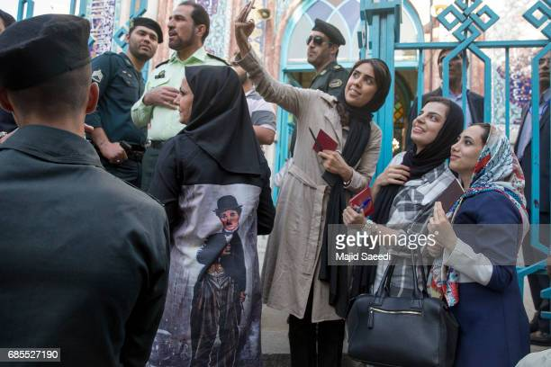 Voters take a selfie as they gather outside a polling station to cast their ballots for the presidential election on May 19 2017 in Tehran Iran...