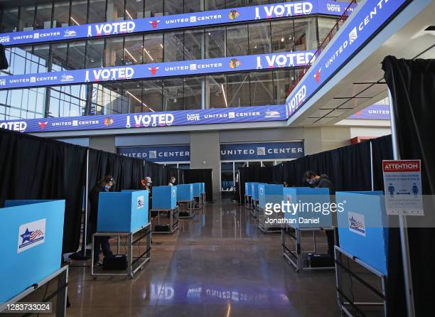 Voters use socially distanced voting machines set up in the east atrium of the United Center where a polling place with 70 machines was set up for...