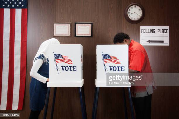 voters voting in polling place - voting booth stock pictures, royalty-free photos & images