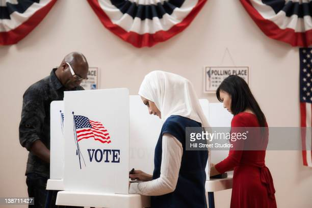 voters voting in polling place - multiculturalism stock pictures, royalty-free photos & images