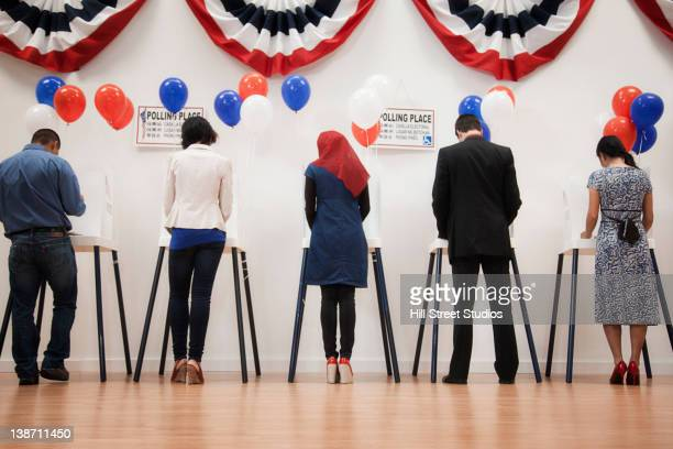 voters voting in polling place - election voting stock pictures, royalty-free photos & images