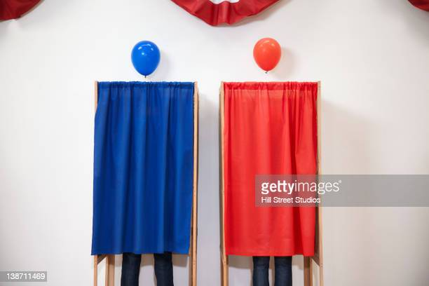 voters voting in polling place - parti politique photos et images de collection