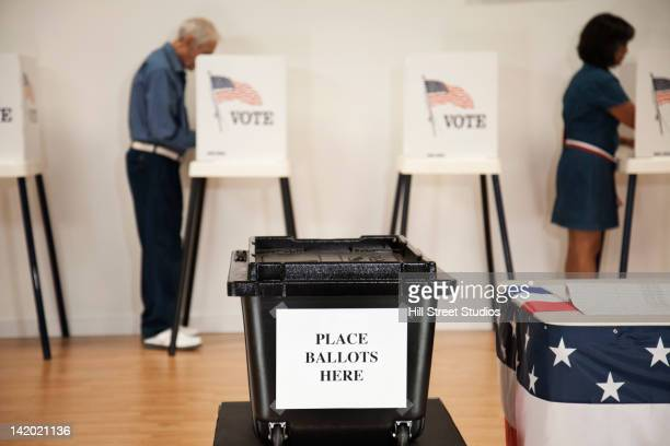 voters voting in polling place - ballot box stock pictures, royalty-free photos & images