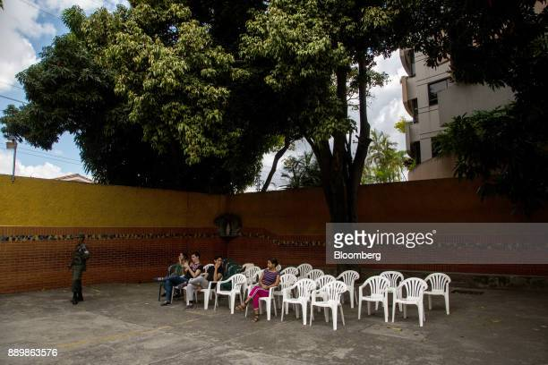 Voters wait as a member of the military stands guard outside a polling station during a nationwide mayoral election in Caracas Venezuela on Sunday...