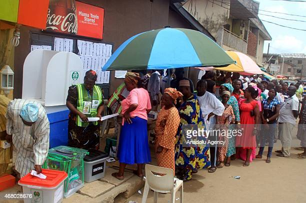 Voters wait in a queue in front of the election centre in the city of Lagos Nigeria on March 29 2015 The parliamentary and state ministerial...