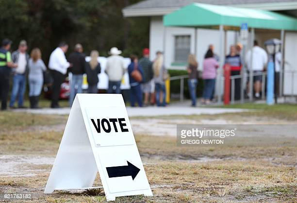 Voters wait in a queue to cast their ballots in the presidential election at a polling station in Christmas Florida on November 8 2016 Polling...