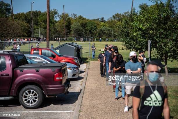 Voters wait in line at a polling location on October 13, 2020 in Austin, Texas. The first day of voting saw voters waiting hours in line to cast...