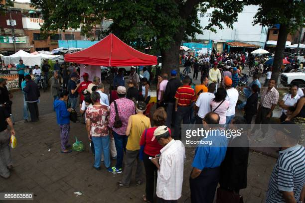 Voters wait in line outside a polling station to use government issued 'Carnet de La Patria' electronic identity cards to register to vote during a...