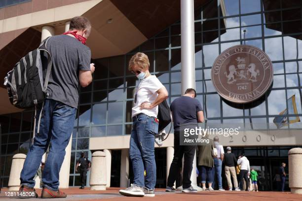 Voters wait in line outside an early voting location at Fairfax County Government Center to cast their votes for the November 3, 2020 elections on...