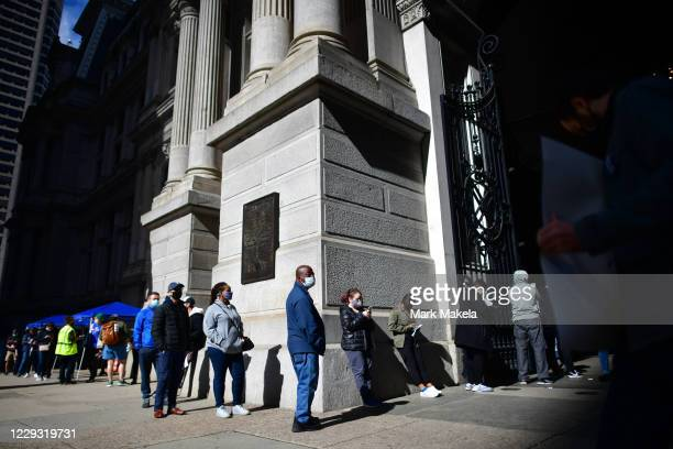 Voters wait in line outside Philadelphia City Hall to cast their early voting ballots at the satellite polling station on October 27, 2020 in...
