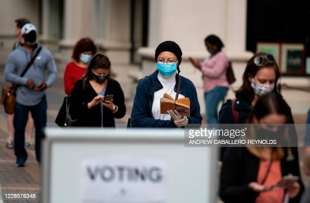 Voters wait in line to cast their ballots for the 2020 election at an early inperson voting location in Arlington Virginia on September 18 2020