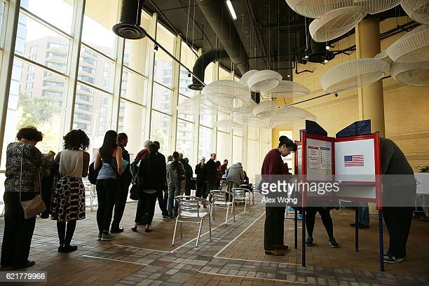 Voters wait in line to cast their ballots in a polling place on Election Day November 8 2016 in Arlington Virginia Americans across the nation pick...
