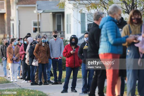 Voters wait in line to cast their ballots on the final day of early voting for the 2020 presidential election on November 2, 2020 in Cedar Rapids,...