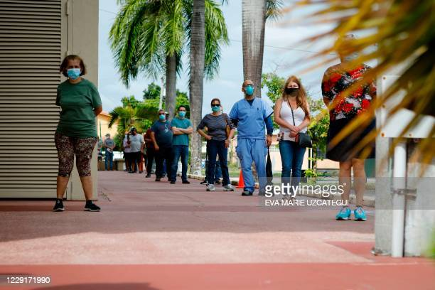 Voters wait in line to cast their early ballots at John F. Kennedy Public Library in Hialeah, Florida on October 19, 2020. - Early voting kicked off...