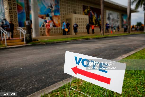 Voters wait in line to cast their early ballots at John F Kennedy Public Library in Hialeah Florida on October 19 2020 Early voting kicked off Monday...