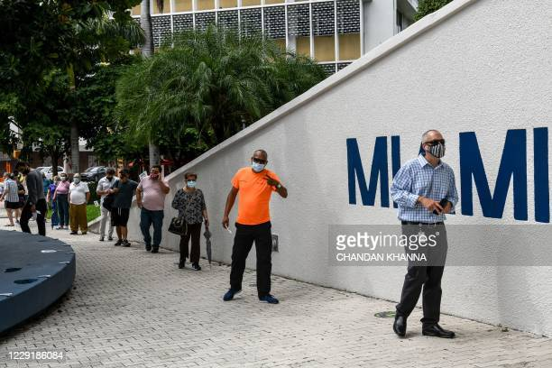 Voters wait in line to cast their early ballots at Miami Beach City Hall in Miami Beach, Florida on October 20, 2020. - With two weeks to go until...