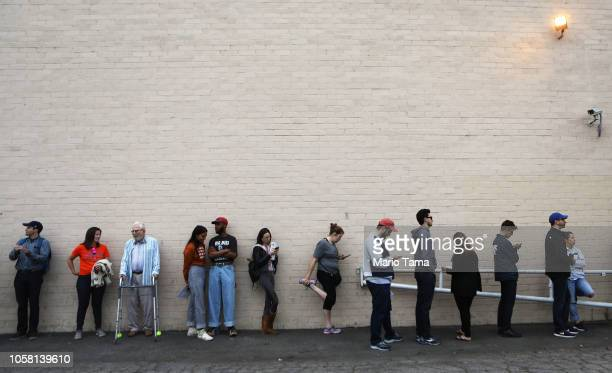 Voters wait in line to caste their ballots in the midterm elections minutes before the polls open on November 6, 2018 in Los Angeles, United States....