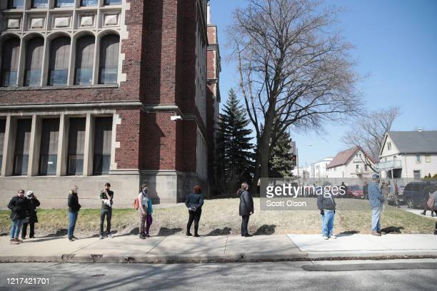Voters wait in line to enter a polling place at Riverside University High School on April 07 2020 in Milwaukee Wisconsin Voters waited in line about...