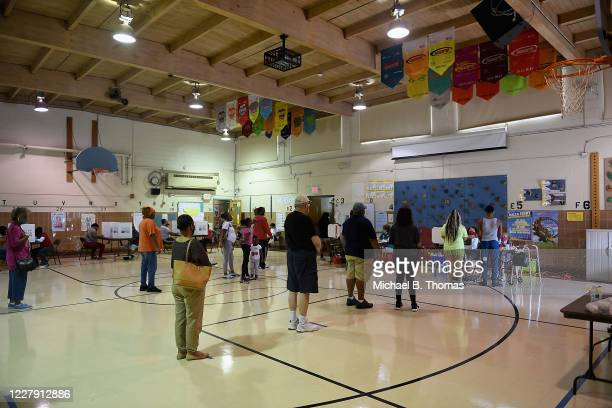 Voters wait in line to vote inside the gymnasium at Halls Ferry Elementary on August 4, 2020 in Florissant, Missouri. Primary voters in Arizona,...