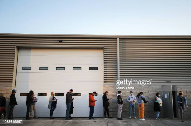 Voters wait in line with social distance to cast their ballots on the final day of early voting for the 2020 presidential election on November 2,...