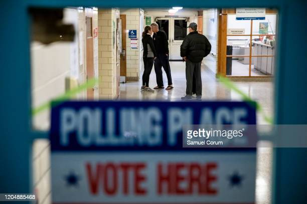 Voters wait outside of the gymnasium for polls to open in the Madison Community Center polling place open on Super Tuesday for the Democratic...