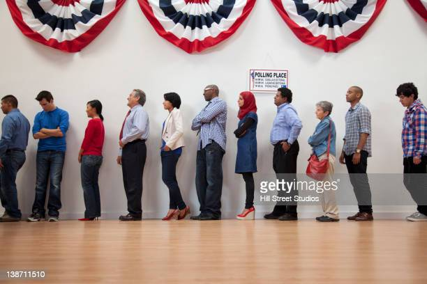 voters waiting to vote in polling place - election voting stock pictures, royalty-free photos & images