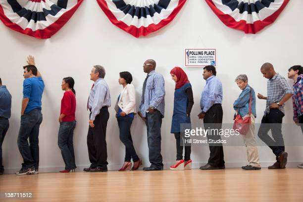 voters waiting to vote in polling place - lining up stock pictures, royalty-free photos & images