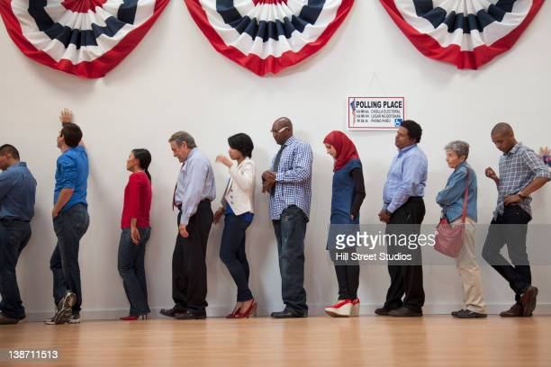 voters waiting to vote in polling place - demokratie stock-fotos und bilder