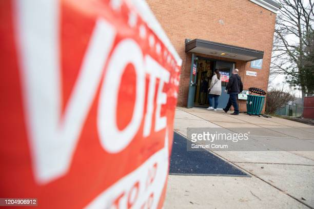 Voters walk into the polling location at Taylor Elementary School to cast their ballots in the Democratic presidential primary elections on Super...