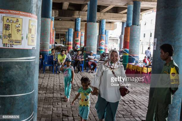 Voters walk out of the polling station after casting their vote for the Jakarta Governal Election on February 15 2017 in Jakarta Indonesia Residents...