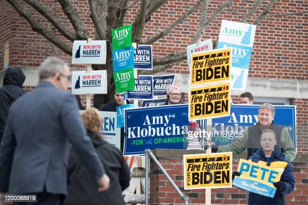 Voters walk past a contingent of people holding signs for presidential candidates outside of the Webster Elementary School polling location during...