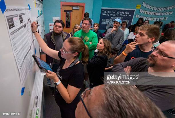 Voters watch as a volunteer counts votes during the Nevada caucuses to nominate a Democratic presidential candidate at the caucus polling station...
