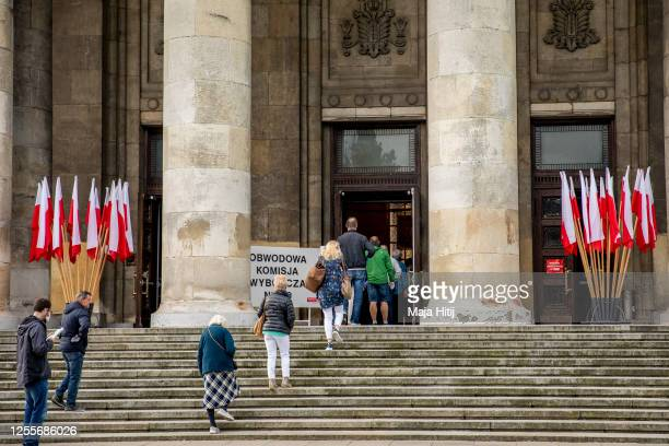 Voters wearing protective face masks line up to vote during Poland's Presidential election runoff on July 12 2020 in Warsaw Poland The latest polls...