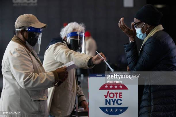 Voters wearing protective masks and face shields drop off absentee ballots at an early voting polling location for the 2020 Presidential election at...