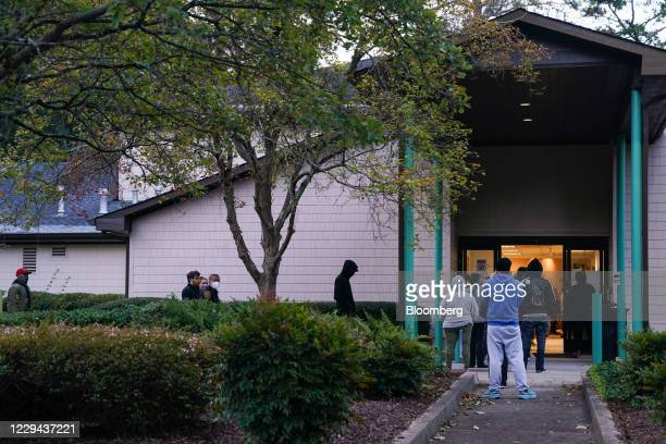 Voters wearing protective masks wait in line outside a polling location for the 2020 Presidential election in College Park, Georgia, U.S., on...