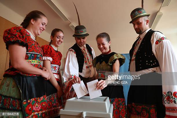 Voters wearing traditional 'Matyo' cast their ballots at a polling station in Mezokoevesd eastern Hungary on October 2 2016 Hungarians vote in a...