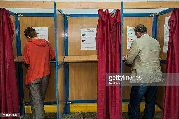 Voters write their chosen candidates in the ballots inside a private space of the polling station during the presidential elections in Poland