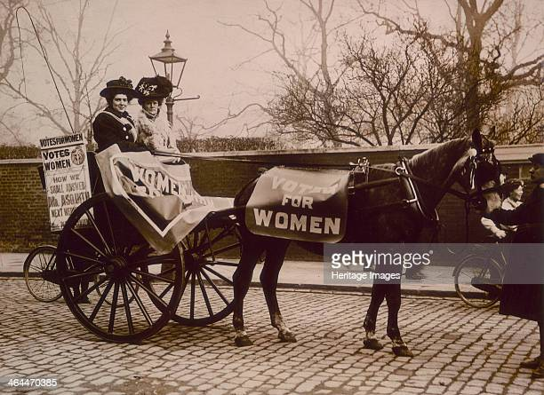 'Votes for Women' demonstration c1910 Two women in a carriage with posters advertising the newspaper Votes for Women Herbert Asquith the Liberal...