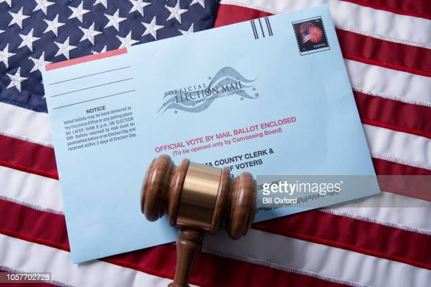 voting ballot: absentee voting by mail with ballot envelope on usa flag and gavel - absentee ballot stock pictures, royalty-free photos & images