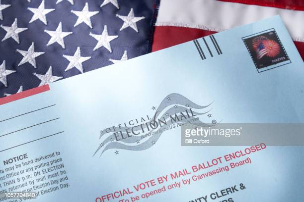 voting ballot: absentee voting by mail with ballot envelope on usa flag - absentee ballot stock pictures, royalty-free photos & images