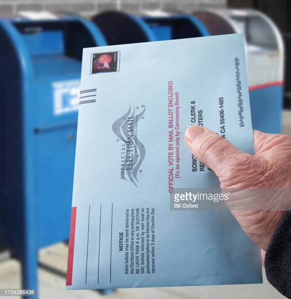 voting ballot: absentee voting by mail with hand holding envelope by mailboxes - absentee ballot stock pictures, royalty-free photos & images