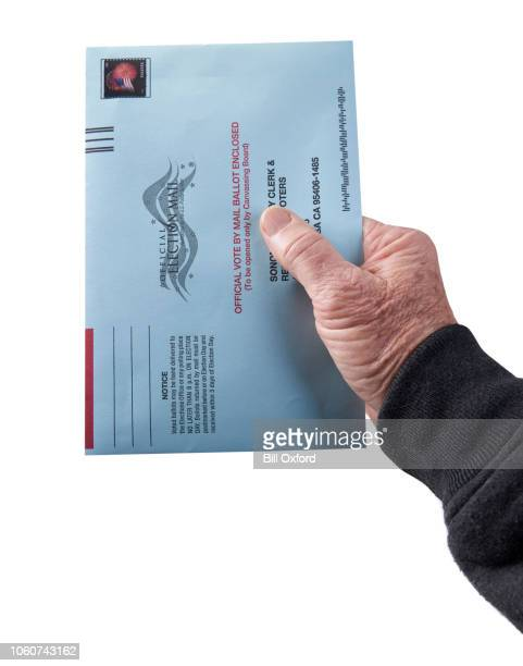 voting ballot: absentee voting by mail with hand holding envelope on white background - absentee ballot stock pictures, royalty-free photos & images