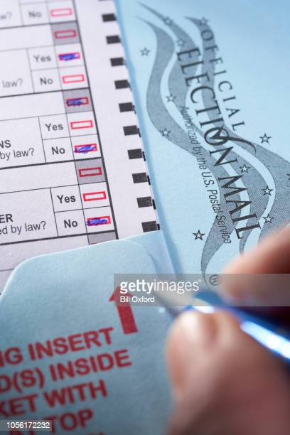 voting ballot: absentee voting by mail with man filling in choice for election and approval of measures - absentee ballot stock pictures, royalty-free photos & images