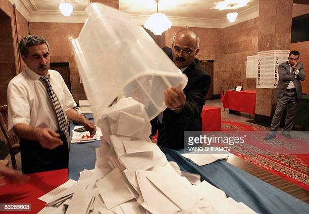 Voting commission officials empty a ballot box to begin counting for Azerbaijan's presidential election at a polling station in Baku on October 15...