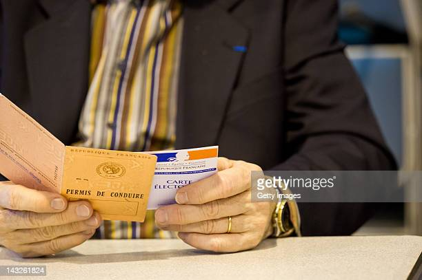 A voting identity card is checked at a polling station during the first round of the 2012 French Presidential election at Voting office number 10 on...