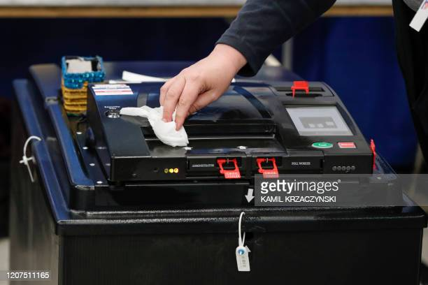 Voting machine is cleaned during the Illinois Democratic primary in Chicago, Illinois, on March 17, 2020.