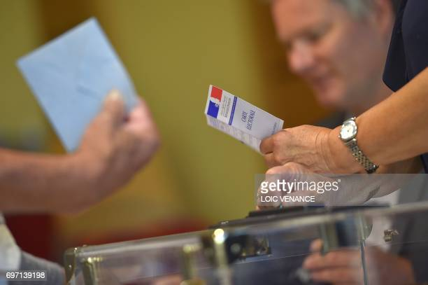 A voting official holds a voter registration card at a polling station in Vertou western France during the second round of the French parliamentary...